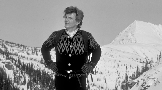Close-up black and white photograph of man with ski poles standing at summit of mountain.