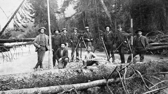 10 men with surveying equipment pose for black and white photo on snow covered ground in a forest.