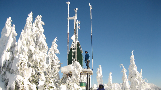 Avalanche technician standing on Great Bear weather station, Coquihalla, BC
