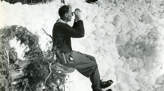 Black and white photograph of man sitting on log in snow looking up a slope with specialized equipment.