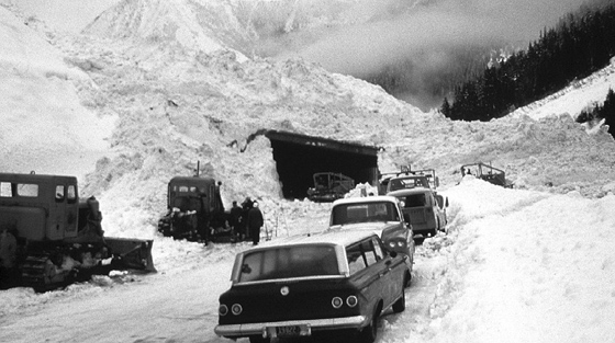Black and white photograph of several vehicles and 3+ snow ploughs lined up outside avalanche covered snowshed.