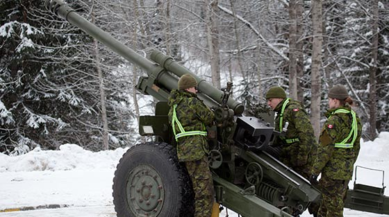 Colour photograph of 3 Canadian army professionals operating howitzer in snow covered valley.