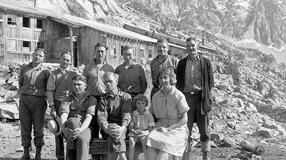 8 men, 1 woman and 1 child pose for black and white photograph with large sheds in background.