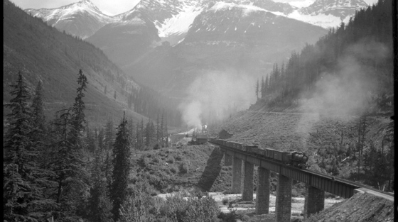 Black and white photograph of train crossing bridge in mountain pass.