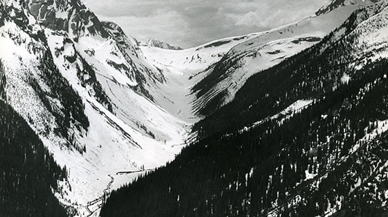Black and white aerial view of valley surrounded by steep mountains in winter.