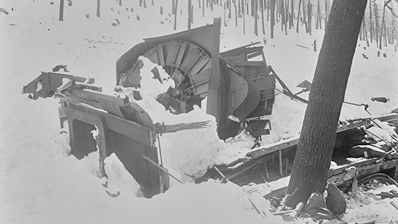 Black and white photograph of mangled rotary snow plough covered in avalanche debris.