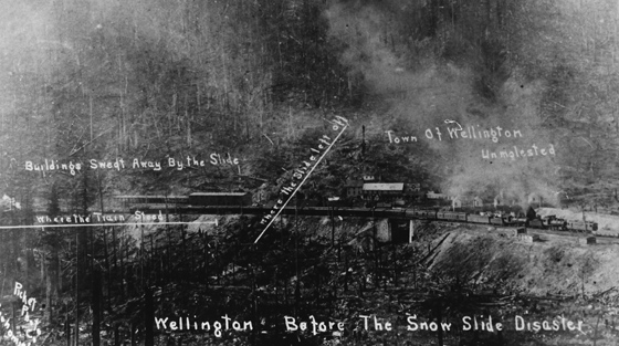 Faded black and white photograph of train station with hand-written annotations pointing out where avalanche struck.