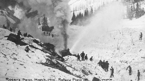 Black and white photograph of 20+ rescuers and rotary plough clearing avalanche debris.