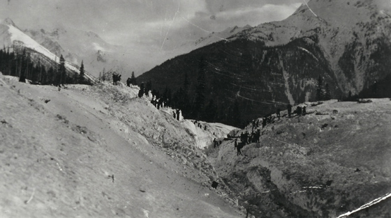 Black and white photograph of disaster site looking from the summit of mountain pass.