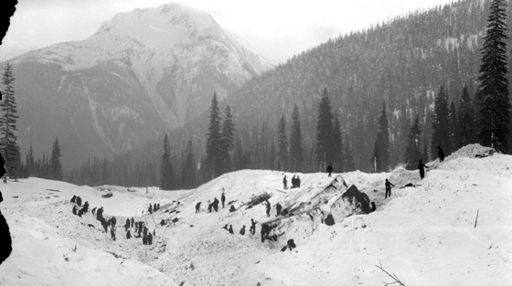 Black and white photograph of 20+ rescuers searching for victims in avalanche debris.