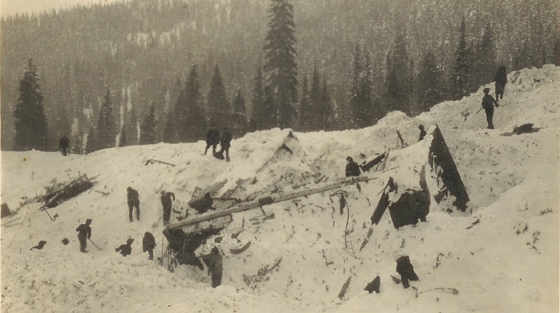 Close-up black and white photograph of 10+ rescuers digging through avalanche debris on slope.