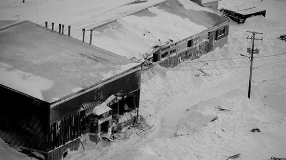 Black and white aerial photograph of two damaged buildings and avalanche debris.