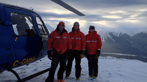 Three rescuers in red jackets stand for colour photograph in front of blue rescue helicopter on mountain top.