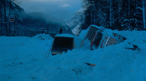 Blue-tinted colour photograph of two overturned vehicles covered in avalanche debris in mountain valley.