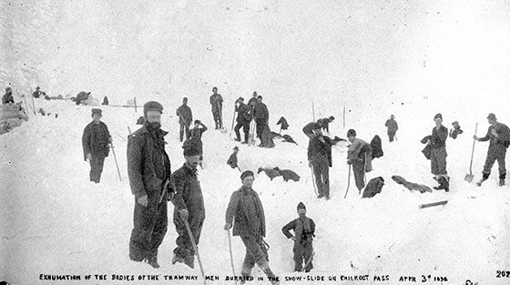At least 20 men with shovels stand still for black and white photograph on the site of fatal snowslide.