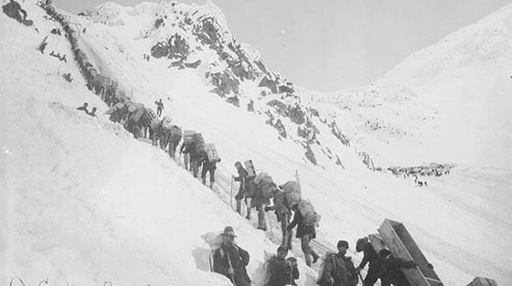 Black and white photograph of dozens of men with packs hiking in line up steep, snow-covered mountain slope.