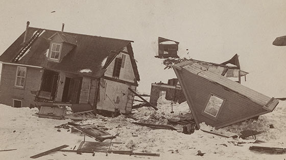 Black and white photograph of the remains of two-storey house in snow, cut in two with roof stripped off.