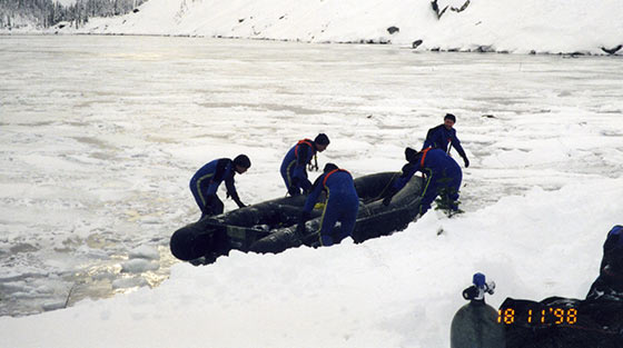 Colour photograph of 5 members of police dive team as they manoeuvre black inflatable boat onto ice covered lake.