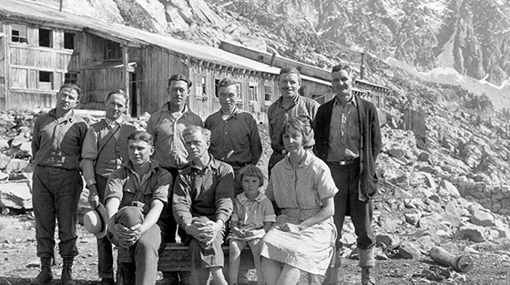 8 men, 1 woman and 1 child pose for black and white photograph with building in background, in summer.