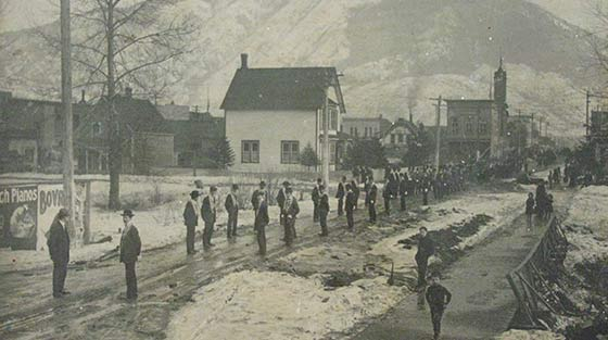 Black and white photograph of 100 + people lining up for funeral procession on street in snow.