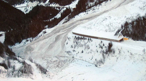 Aerial, colour photograph of avalanche partially blocking river and highway in mountain pass.